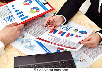 employees discussing business chart in office