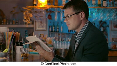 Businessman with Tablet in the Bar
