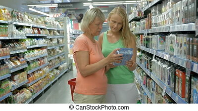 Adult Mother and Daughter in the Food Shop - Adult mother...