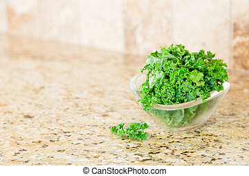 A bowl of fresh green kale on a granite countertop