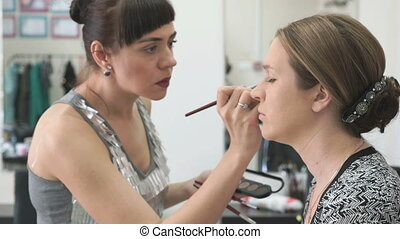 The visage master making make-up for young model -...