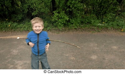 Happy little boy plays with rod laughs and smiles - Happy...