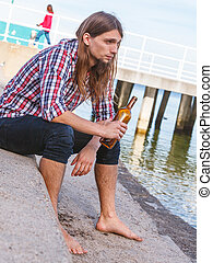 Man depressed with wine bottle sitting on beach outdoor -...