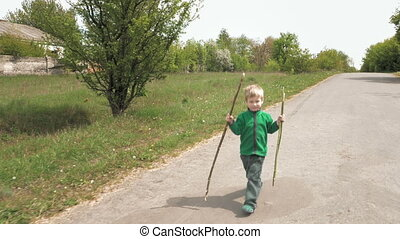 Happy little boy plays with rod walks outdoor road