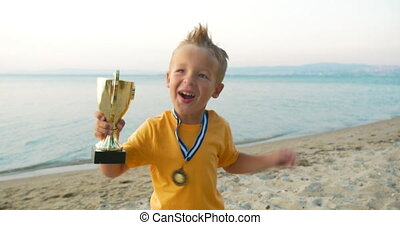 Happiness of being the champion - Little child with cup and...