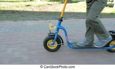 Child rides push kick scooter fast in summer park - Child...