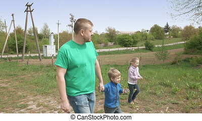 Father and happy children walk together outdoor