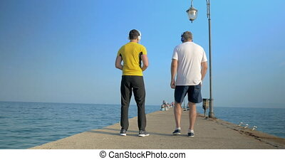 Men exercising by walking backward along the pier -...