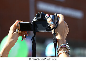 Camera in women\'s hands - Women\'s hands with bracelets and...