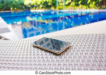Smartphone put on armchair beside the pool means to get...