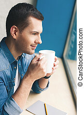 Attractive young guy is enjoying hot drink - Handsome man is...