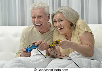 Senior couple playing video game - happy Senior couple...