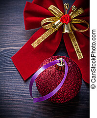 Christmas bow bauble on wooden board holidays concept