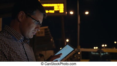 Man with tablet computer on bus station at night - Young man...