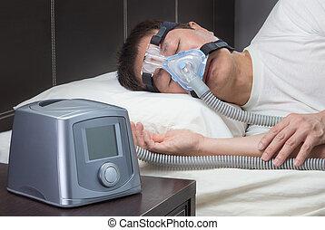 Asian man with sleep apnea using CPAP machine, wearing...
