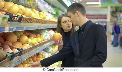 Happy couple choosing grapefruits in a supermarket, full HD