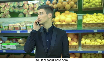 Man speaking on the phone in a supermarket and girl...
