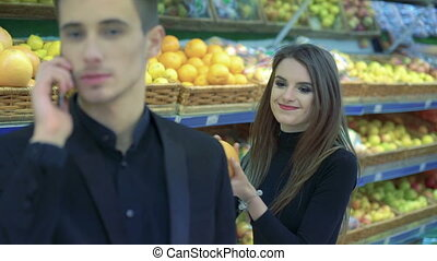 Couple in supermarket. Boy speaking on a phone, girl with fruit distracting boy