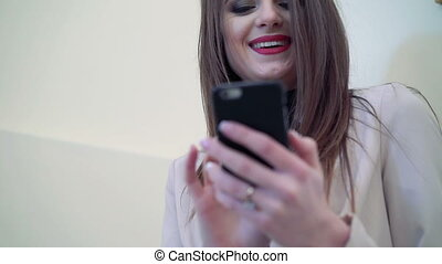 Young woman with red lips  smilimg and using phone.