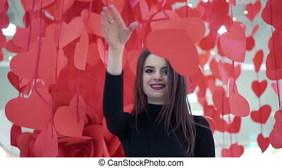 Pretty woman posing on the background of red hearts and smiling