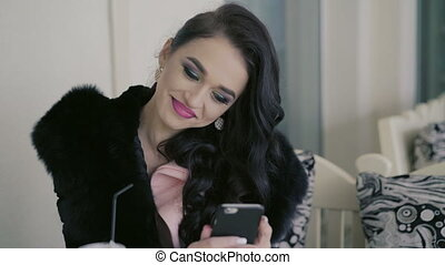 Smart brunette in expensive fur drinking juice, looking on the phone in cafe. 4K