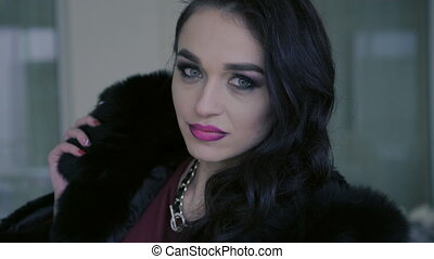 Closeup of portrait of smart woman in expensive fur poses to the camera. 4K