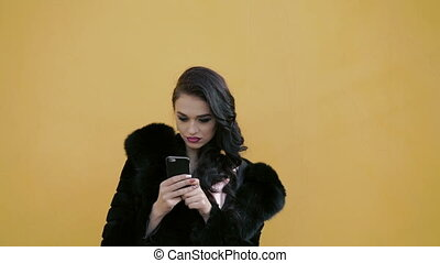 Pretty lady in the fur using smartphone and looking on the sky