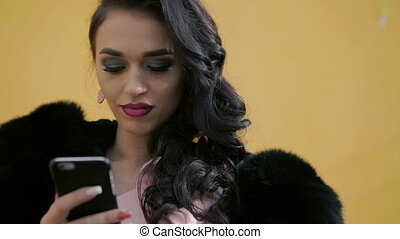 So smart lady in fur using phone.