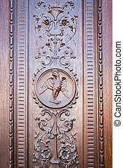 Eagle engraved on the wooden portal of an ancient church -...