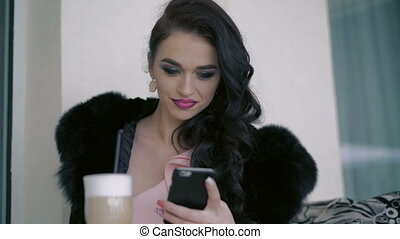 Glamorous lady drinking latte seductively, using phone in...