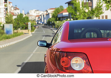 Car parked beside the road in town. - Red car on a city...