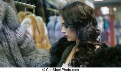 Glamorous woman looking on the fur coat in the shop.