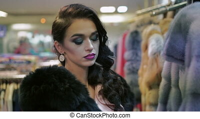 Seductively woman choosing fur coat in fashion shop