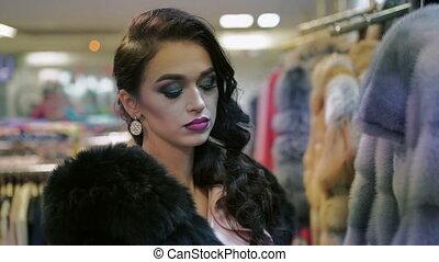 Seductively woman choosing fur coat in fashion shop