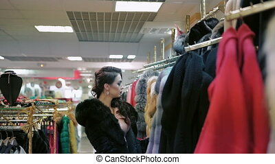 Elegant lady looking on the fur coat in the shopping center.