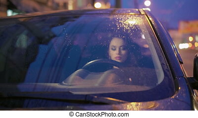 Smart lady sitting in the black car when raining.