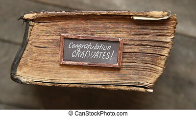 congratulations graduates text and vintage book on table -...