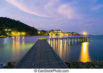 Wooden bridge walkway leading to the sea night view, with...
