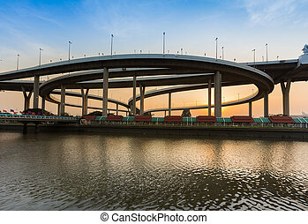 Round interconnection river front with sunset sky background