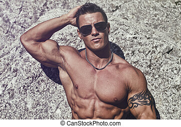 Attractive young muscle man shirtless against white rocks,...