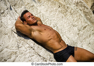 Handsome young man laying naked on white rocks, eyes closed