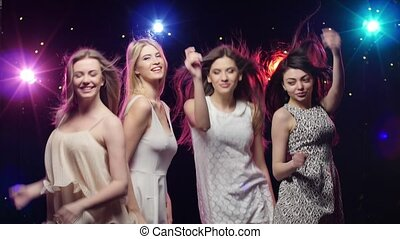 Young smiling girls are dancing. Stroboscope lamps provide...