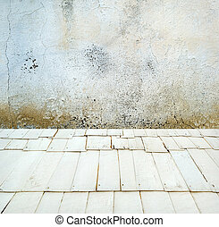 Room interior: grey old painted cement wall with wooden floor