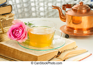Cup of tea with books - Tea in glass cup with teapot, open...