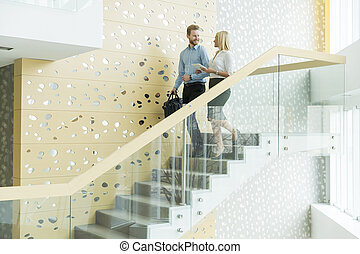 Couple on the office stairs - Young couple on the stairs in...