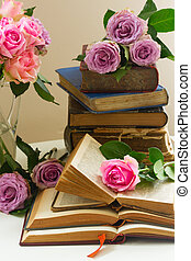 Old books with rose flower - Pile of old books with bouqet...