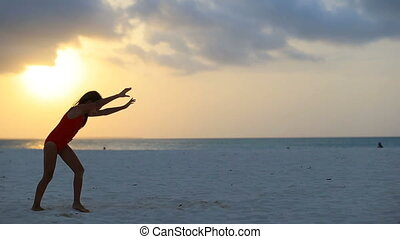 Silhouette of adorable active little girl on white beach at sunset