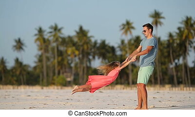 Little girl and dad during tropical beach vacation