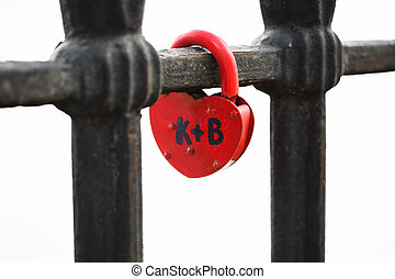 Closed red padlock in the form of heart locked on bridge.