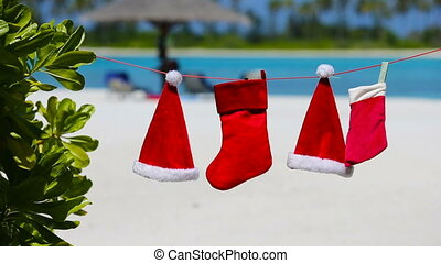 Red Santa hats and Christmas stocking hanging on tropical...